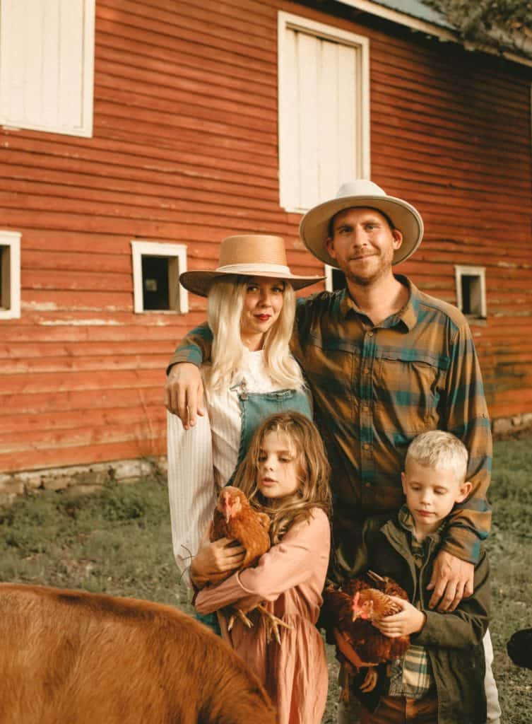 Britnye & Cody Shore and their two young children pose in front of their stunning farmhouse