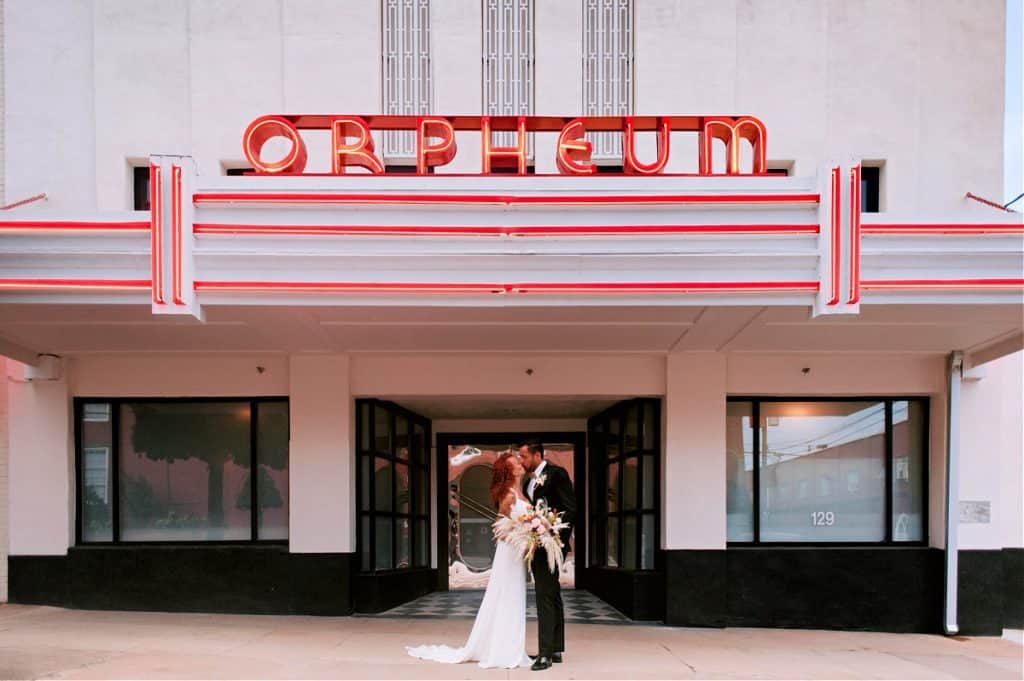 A newly-wed bride and groom share a kiss in in front of the Orpheum Theater
