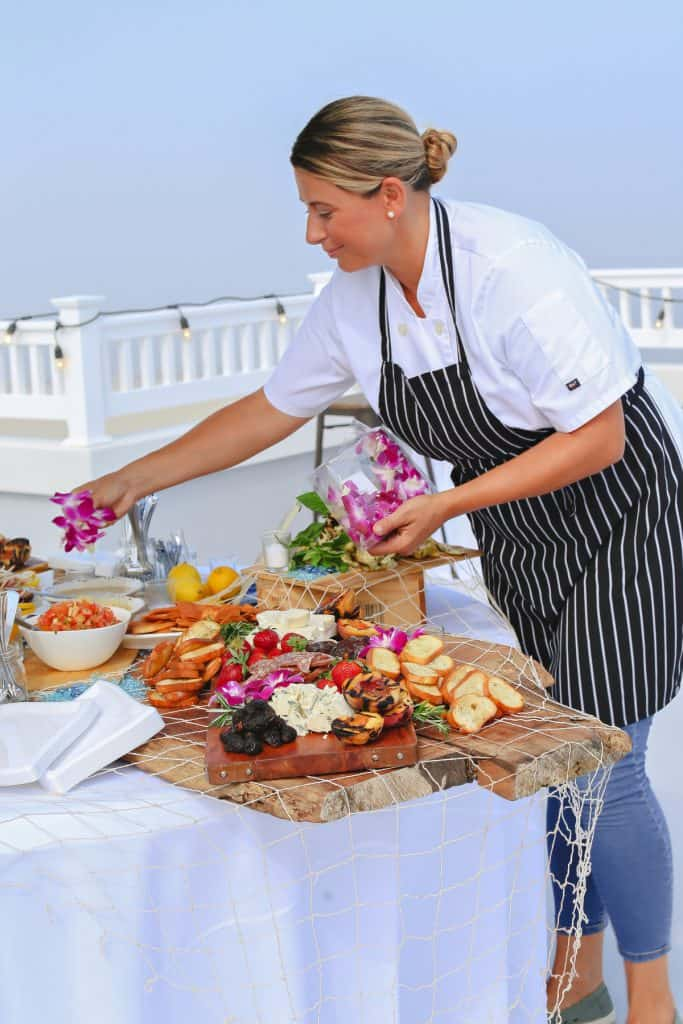 Owner of Chef Covas Catering in Long Branch, NJ garnishing rustic antipasto display at seaside party